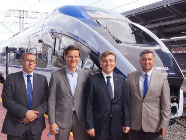 cztery osobie na tle nowoczesnego pociągu