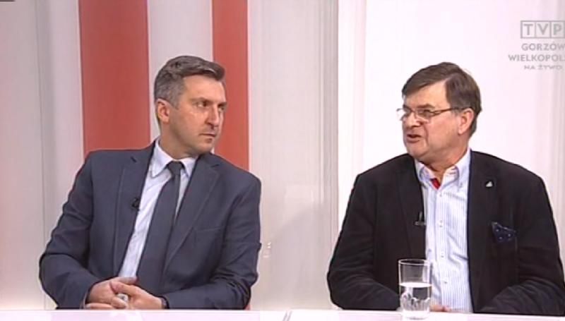 dwóch mężczyzn siedzi przy stole i rozmawia